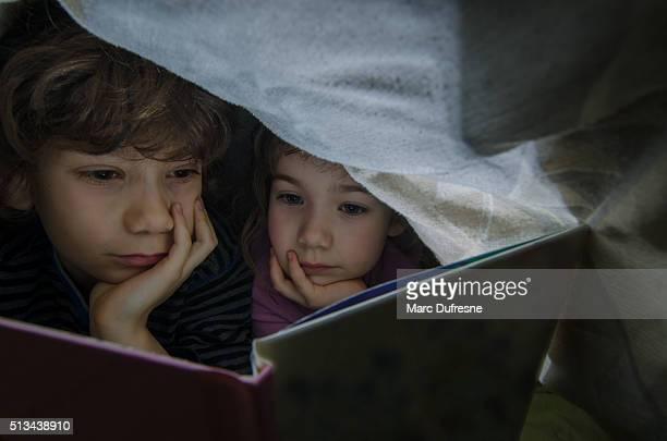 Piccolo ragazzo e ragazza lettura sotto le lenzuola prima di dormire