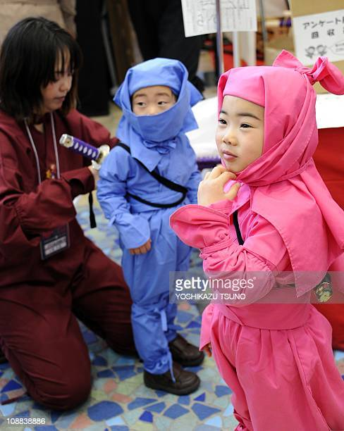 A little boy and girl smile as they try on 'ninja' costumes during a festival at a shopping mall in Tokyo on February 5 2011 Some 80 people in ninja...