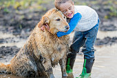 An elementary age boy is playing outside in the mud with his pet golden retriever. The little boy and the dog are covered in mud.
