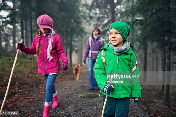 Little boy and his family hiking in cold misty forest