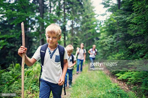 Little boy and his family hiking in forest