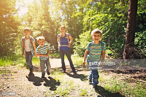 Little boy and his family hiking in sunny forest