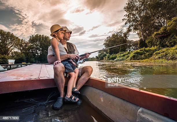 Petit garçon et son père de pêche en eau douce en bateau.