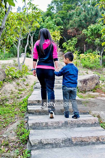 Little boy and his mother climbing stairs