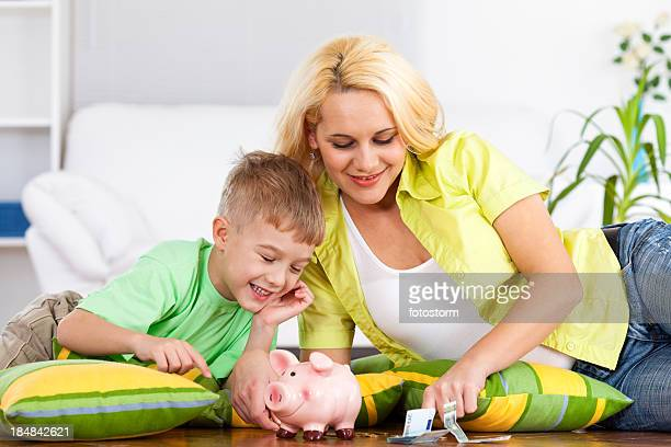 Little boy and his mother inserting money into piggy bank