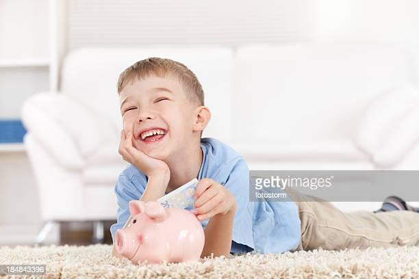 Jungen und seine Mutter Eingabe in das Sparschwein Geld