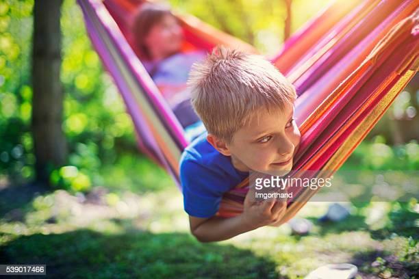 Kleiner Junge und seine Schwester spielen auf Hängematte