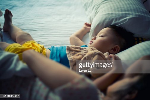 Little boy and mother sleep on bed : Stock Photo