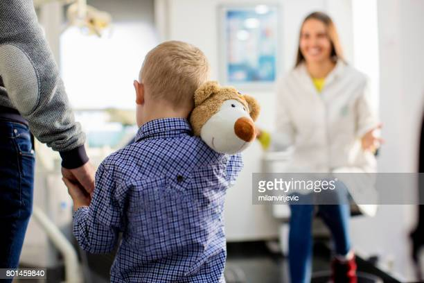 Little boy arriving at dentists office with teddy bear