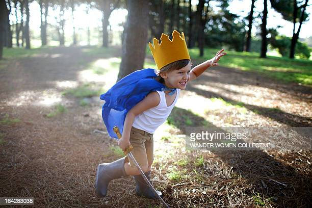 LIttle boy as prince in crown with sword in forest