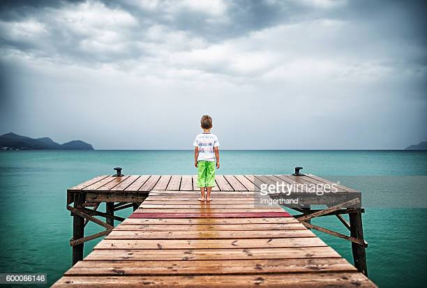 Little boy at sea pier