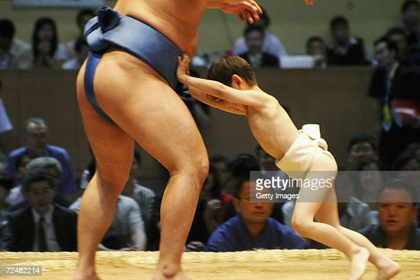 A little boy attempts in vain to push a professional sumo wrestler before a sumo tournament on June 5 2004 in Beijing China A total of 111 sumo...