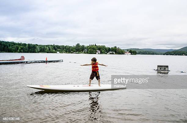 Little boy balancing on surf board