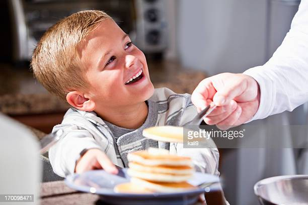 Little boy being served pancakes for breakfast