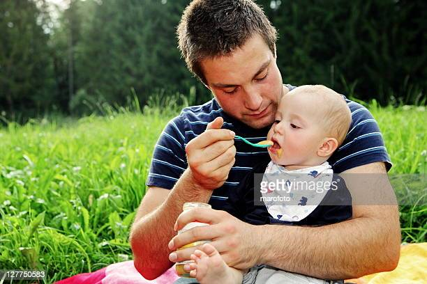 Little boy being spoon fed by father in field