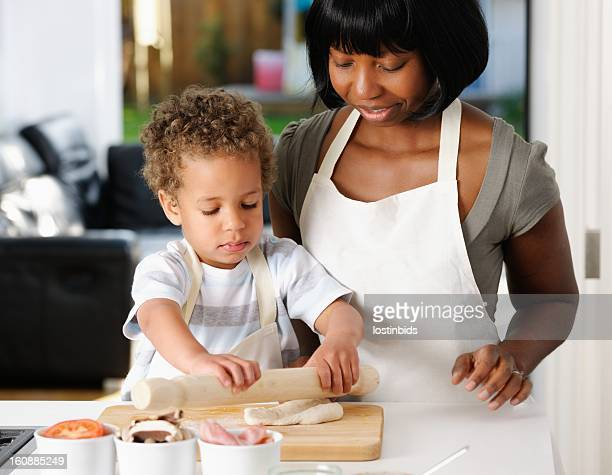 Little Boy Being Supervised By Carer/ Mother Rolling Pizza Dough