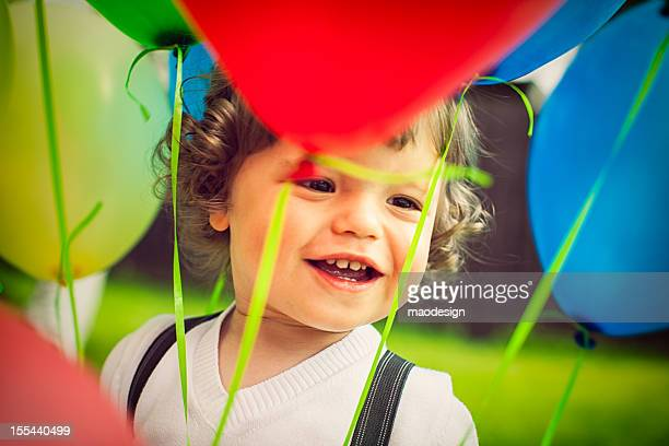 Little boy between colorful balloons.