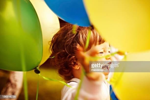 Petit garçon entre ballons colorés.