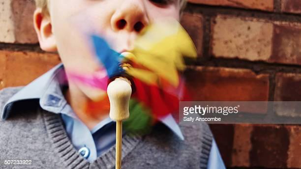 Little boy blowing a toy windmill