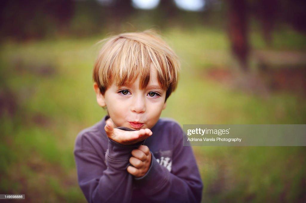 Little boy blowing kiss