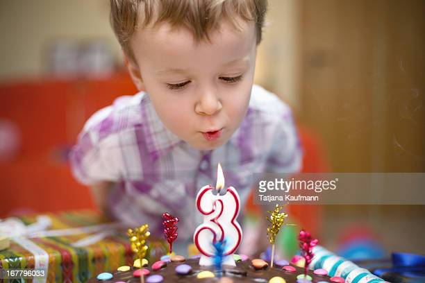 Little Boy blowing out Candle on his Birthday