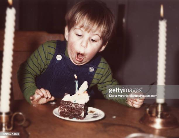 little boy blowing out his first birthday candle