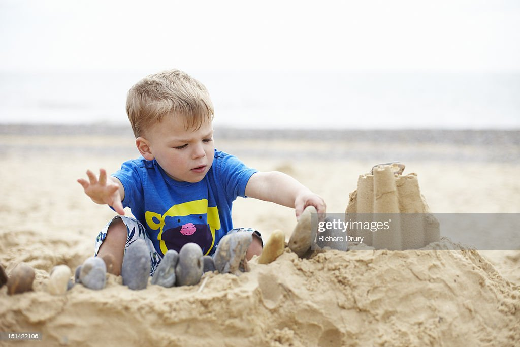 Little boy building sandcastle : Stock Photo