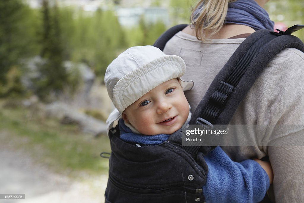 little boy carried at the back of the mother : Stock Photo