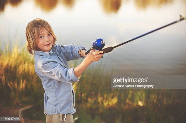 Little boy casting fishing pole into lake