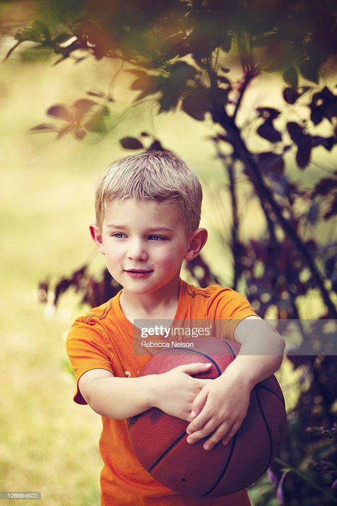 Little boy casually holding basket ball : Stock Photo