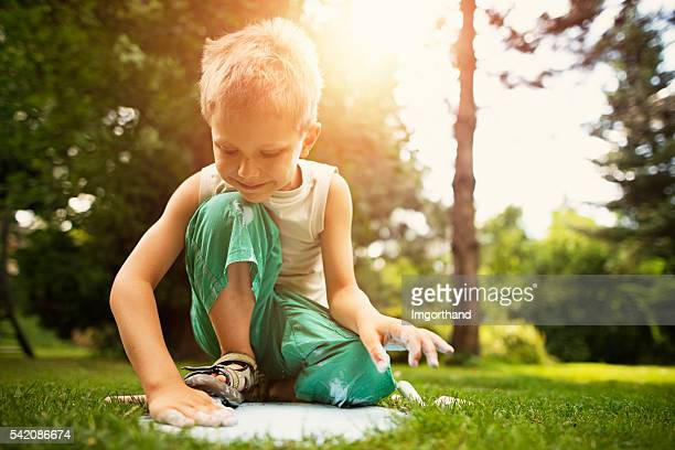Kleiner Junge kreidung im Garten