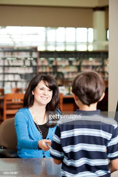 Petit garçon qui quittent l'établissement un livre de la bibliothèque