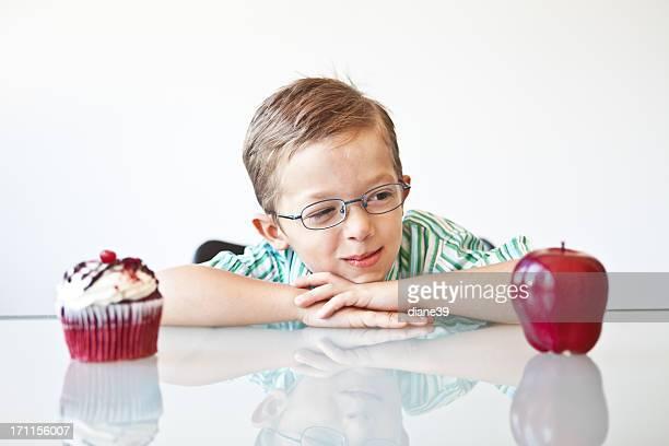 Little boy choosing between a apple and cupcake