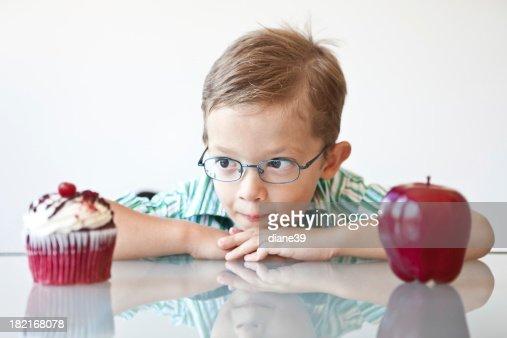 Kleine Jungen, die Wahl zwischen einen Apfel und cupcake und