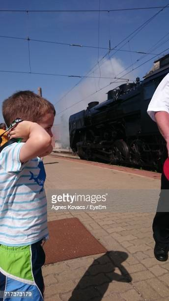 Little Boy Covering Ears At Railroad Station