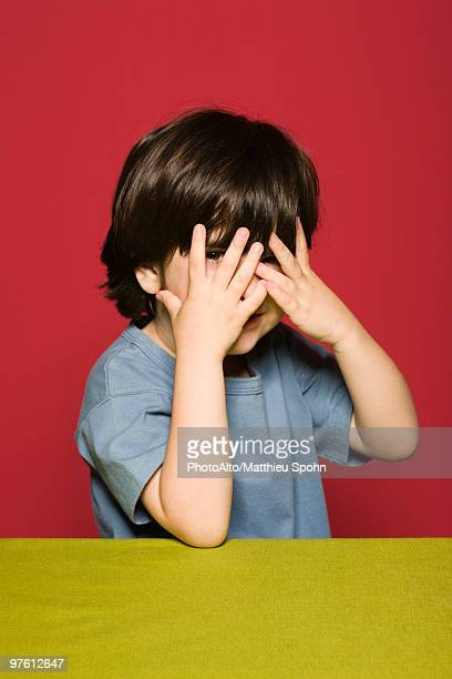 Little boy covering face with hands, peeking through fingers at camera