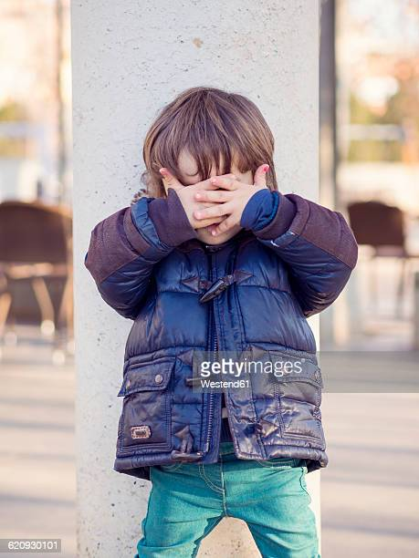 Little boy covering face with his hands