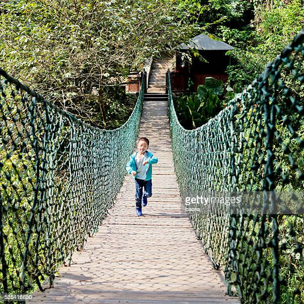 Little boy crossing the rope bridge