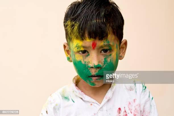 Little boy daubed in Holi colors