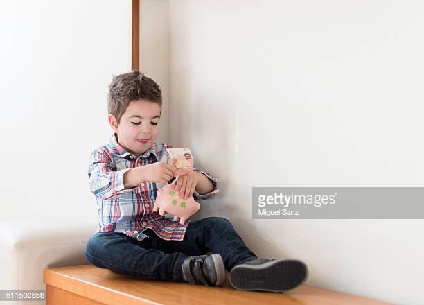 Little boy depositing coin in piggy bank