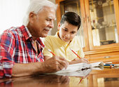 Happy little boy doing school homework with old man at home. Family relationship between grandfather and grandson. Grandpa teaching, male grandchild learning