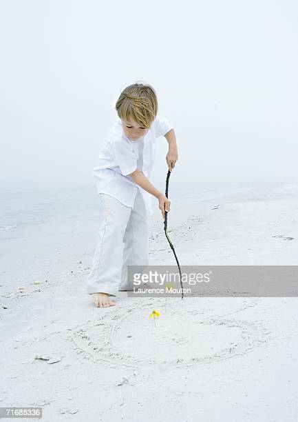 Little boy drawing heart in the sand at the beach
