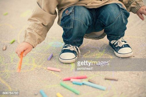 Little boy drawing with sidewalk chalks