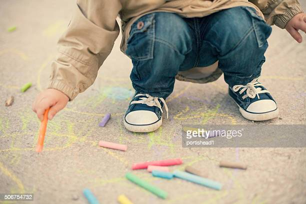 Little boy drawing with sidewalk chalks