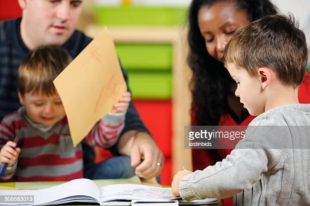 Petit garçon dessin et l'écriture tandis que vos aides-soignants superviser les jeunes enfants