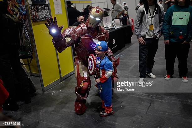 A little boy dressed as Captain America has his photograph taken with the Iron Man as they attend the London Super Comic Convention in the Excel...