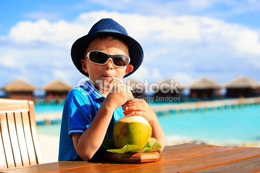 Little Boy Drinking Coconut Cocktail On Tropical Beach Stock Photo