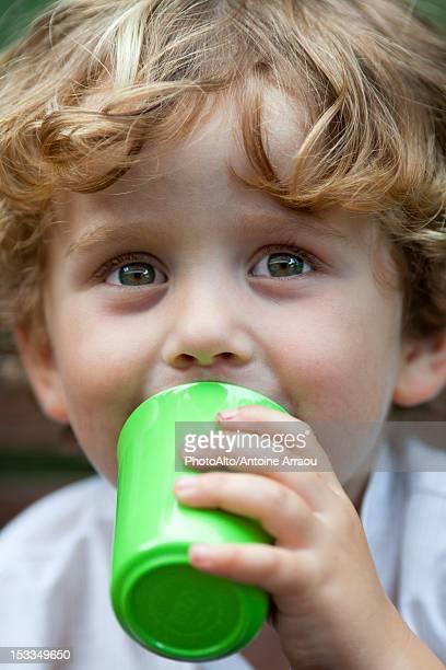 Little boy drinking from cup, portrait