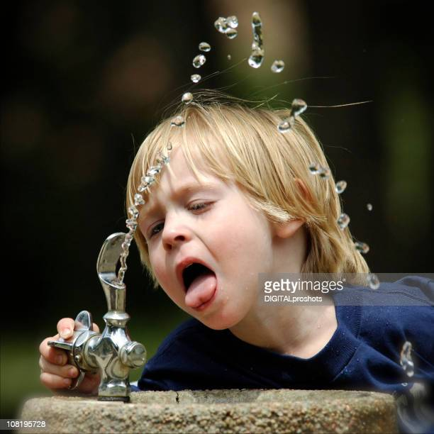 Little Boy Drinking from Water Fountain Outside