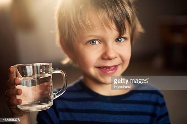 Kleine Junge trinkt ein Glas Wasser.